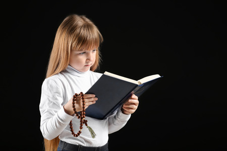 Little girl reading Bible on dark background