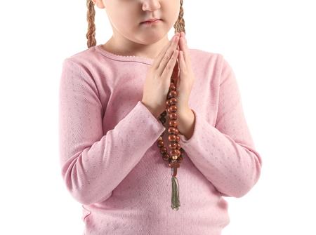 Little girl with beads praying on white background Stock Photo