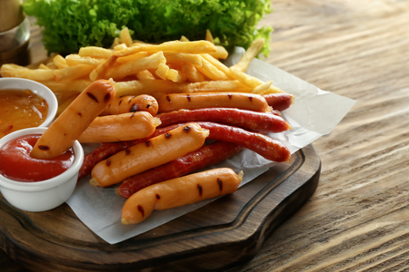 Delicious grilled sausages with sauces and french fries on wooden board Banco de Imagens