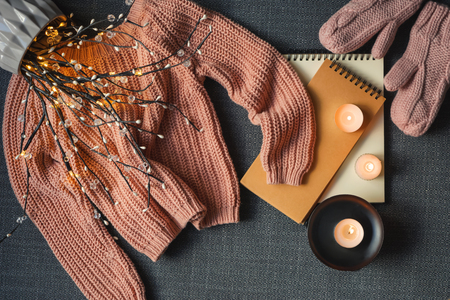 Composition with warm sweater and burning candles on dark background
