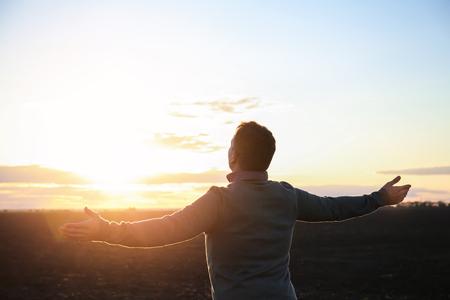 Religious man praying outdoors at sunset 版權商用圖片