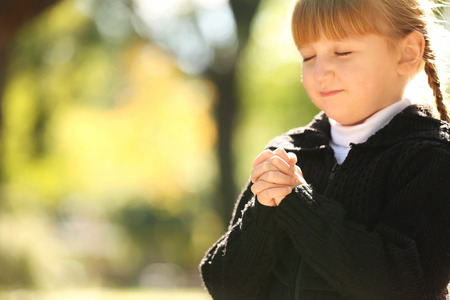 Little girl praying outdoors