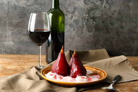 Plate with ice cream and sweet pears stewed in red wine on wooden table