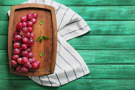 Wooden board with ripe tasty grapes and mint leaves on color table 스톡 콘텐츠