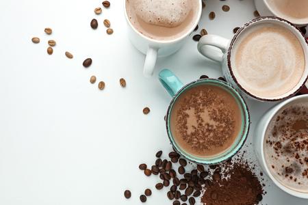 Muchas tazas con sabroso café aromático sobre fondo blanco.