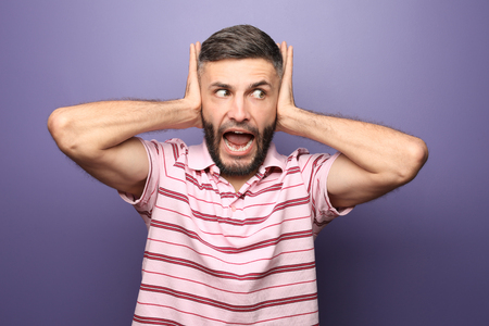 Portrait of emotional man covering ears with hands on color background
