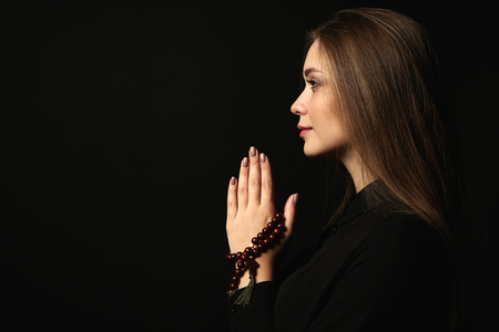 Beautiful young woman praying on dark background