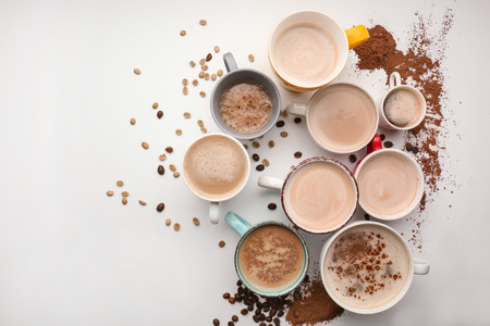 Many cups with tasty aromatic coffee on white background