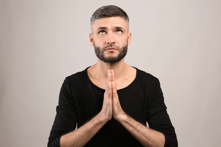 Handsome man praying on grey background
