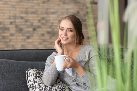 Happy young woman drinking tea at home