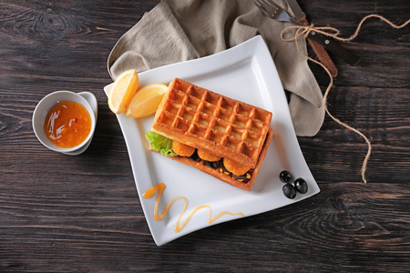 Delicious waffles with chicken nuggets and sauce on wooden table