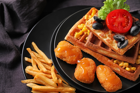 Delicious waffles with chicken nuggets and french fries on plates