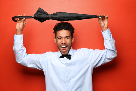 Portrait of happy African-American man with umbrella on color background