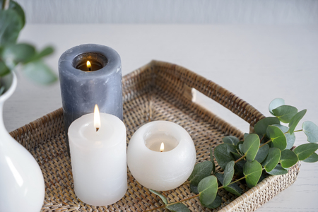 Beautiful burning candles with green leaves on wicker tray