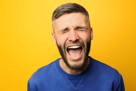 Portrait of screaming man on color background