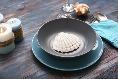 Beautiful table setting with sea shells on wooden background
