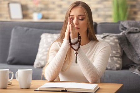 Beautiful young woman praying at home 스톡 콘텐츠