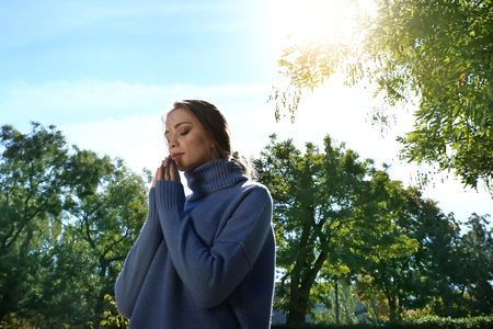 Beautiful young woman praying outdoors