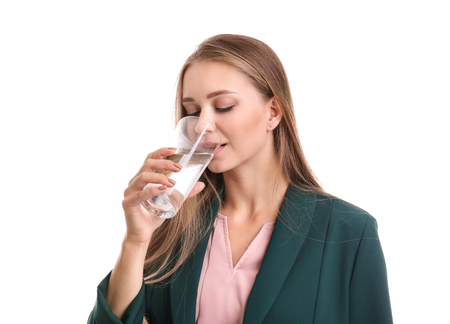 Beautiful young woman drinking water on white background