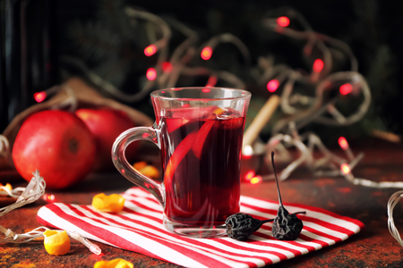Glass cup of delicious mulled wine on color table