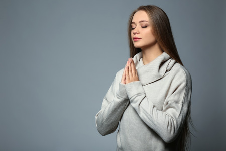Beautiful young woman praying on grey background