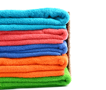 Folded color towels on white background