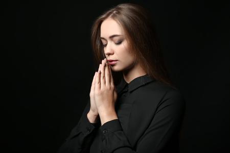 Beautiful young woman praying on dark background