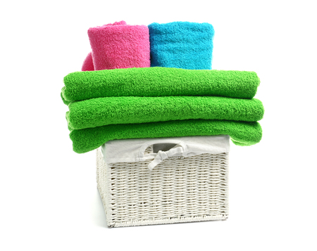 Wicker basket with clean tidy towels on white background