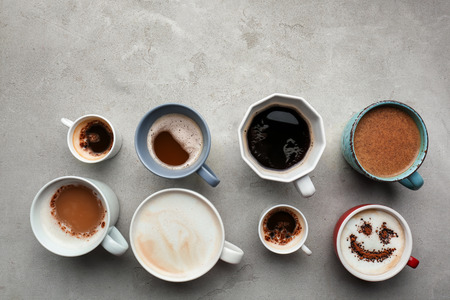 Many cups with tasty aromatic coffee on grey table