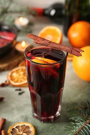 Glass of delicious mulled wine on color table