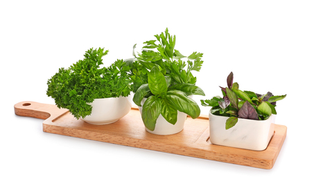 Bowls with fresh aromatic herbs on wooden board, isolated on white
