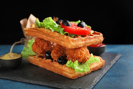 Delicious waffles with chicken and vegetables on slate plate
