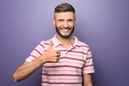 Happy man showing thumb-up gesture on color background 스톡 콘텐츠