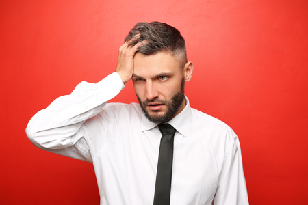 Portrait of tired businessman on color background