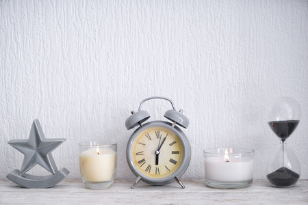 Beautiful burning candles with alarm clock and hourglass on light wooden table Stok Fotoğraf