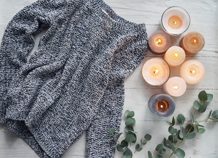 Beautiful burning candles with warm sweater on white wooden table