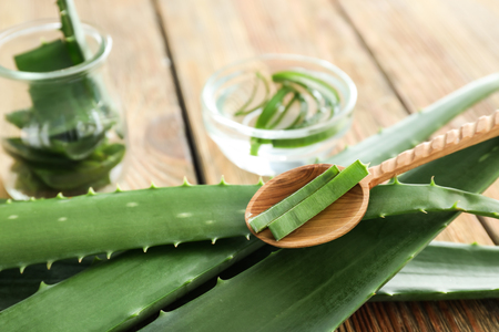 Fresh aloe vera leaves with spoon on wooden table, closeup