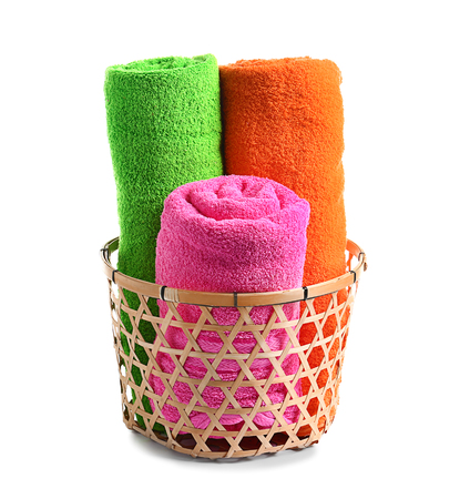 Basket with bright rolled towels on white background