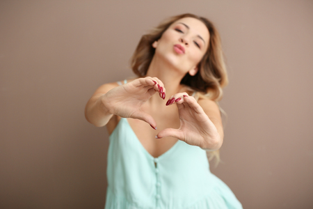 Portrait of beautiful young woman making heart with her hands on color background
