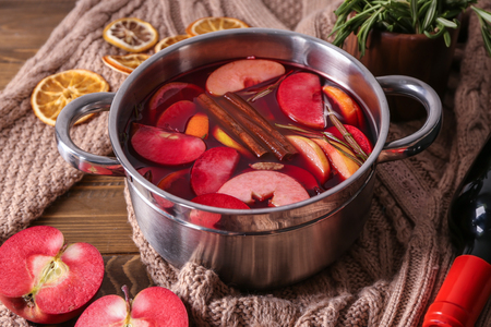 Saucepan of delicious mulled wine with warm sweater on wooden table