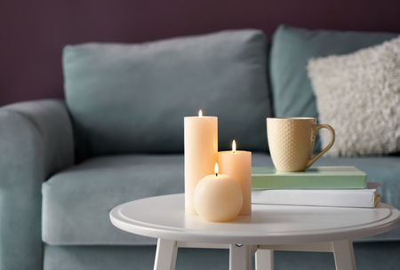 Beautiful burning candles with books on white table indoors
