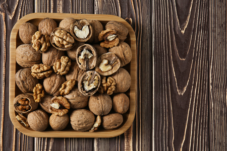 Plate with tasty walnuts on wooden table 스톡 콘텐츠
