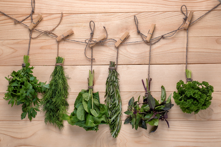 Bunches of different fresh herbs on wooden background