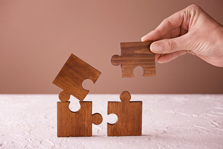 Female hand and pieces of wooden puzzle on table Фото со стока