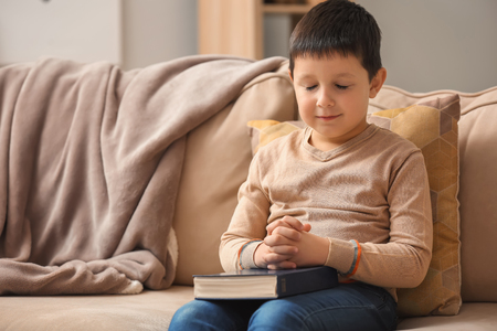 Little boy with Bible praying at home Stock Photo