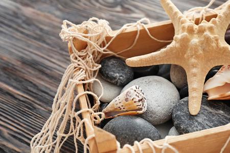 Sea shells and stones in wooden box, closeup