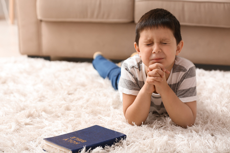 Little boy with Bible praying at home Foto de archivo