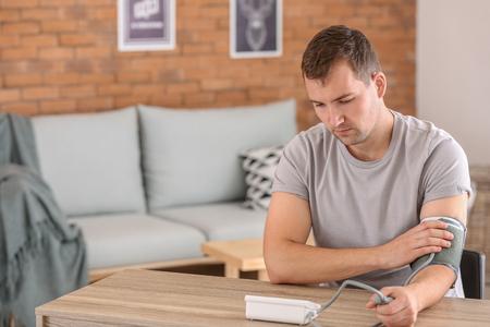 Jeune homme mesurant sa tension artérielle à la maison Banque d'images