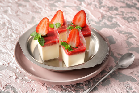 Glasses with tasty strawberry panna cotta on metal tray