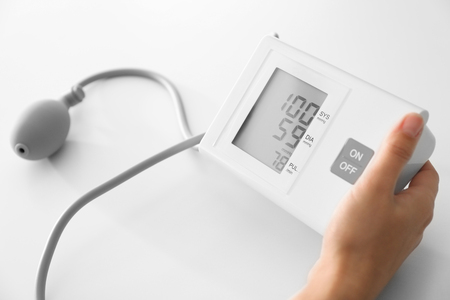 Woman measuring blood pressure with sphygmomanometer on white table Stock Photo